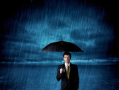Business man standing in rain with an umbrella — Foto de Stock