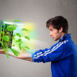 Casual boy holding laptop with recycle and environmental symbols — Stock Photo #58842769