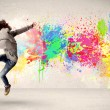 Happy teenager jumping with colorful ink splatter on urban backg — Stock Photo #59001195