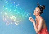 Pretty lady blowing colorful bubbles on blue background — Stockfoto