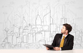 Businessman sitting at the white table with hand drawn buildings — Stock Photo