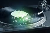 Turntable playing music with audio notes glowing — Stock Photo