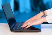 Businessman pressing modern laptop computer on colorful backgrou — Stock Photo