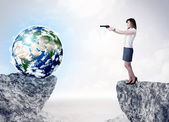 Businesswoman on rock mountain with a globe — Stock Photo