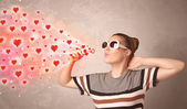 Pretty young girl blowing red heart symbols  — Stock Photo