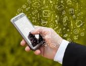 Hand holding smartphone with hand drawn media icons and symbols — Foto de Stock