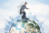Man riding unicycle around the globe with major cities — Stock Photo
