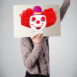 Businessman holding a cardboard with a clown on it in front of h — Stock Photo #60409457