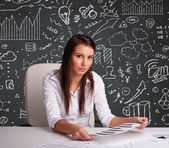 Businesswoman sitting at desk with business scheme and icons — Stock Photo