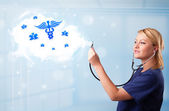 Young doctor with abstract cloud and medical icons — Stock Photo