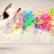 Happy teenager jumping with colorful ink splatter on urban backg — Stock Photo #60578705