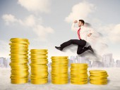 Successful business man jumping up on gold coin money — Stock Photo
