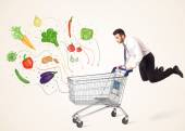 Businessman with shopping cart with vegetables — Fotografia Stock