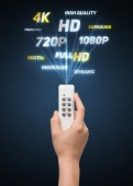 Hand with remote control and multimedia properties — Stock Photo