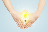 Hands creating a form with light bulb — Stock Photo