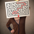 Woman holding a paper with a labyrinth on it in front of her hea — Stock Photo #61604129