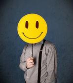 Empresário segurando um emoticon de rosto sorridente — Fotografia Stock