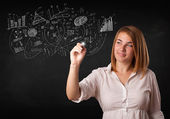 Pretty girl sketching graphs and diagrams on wall — Stock Photo