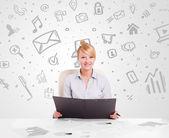 Business woman sitting at table with hand drawn media icons  — Stock Photo