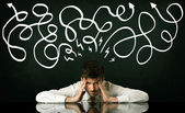 Depressed businessman sitting under drawn direction lines — Stock Photo