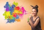 Cute girl blowing colorful splash graffiti  — Stock Photo