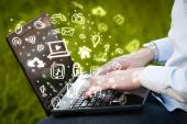 Hand writing on notebook computer with media icons and symbols — Stock Photo