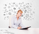 Young businesswoman with all kind of hand-drawn media icons in b — Stock Photo