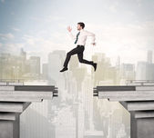 Energetic business man jumping over a bridge with gap — Stock Photo