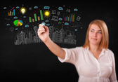 Cute woman sketching city and graph icons — Stock Photo