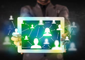 Young person presenting tablet with green social media icons — Stock Photo