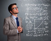 Handsome school boy thinking about complex mathematical signs — Stock Photo
