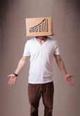 Young man gesturing with a cardboard box on his head with diagra — Stock Photo