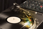 Music player playing vinyl with glow lines comming from the need — Stock Photo