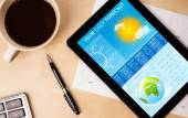 Tablet pc showing weather forecast on screen with a cup of coffe — Stock Photo