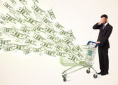 Businessman with shopping cart with dollar bills — Stock Photo
