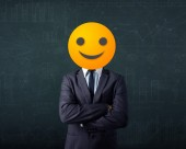 Businessman wears yellow smiley face — Stock Photo