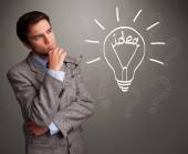 Young boy comming up with a light bulb idea sign — Stock Photo