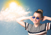 Young person looking with sunglasses at clouds and sun — Stok fotoğraf