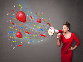 Young girl having fun, shouting into megaphone with balloons  — Stock Photo