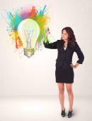 Young lady drawing a colorful light bulb with colorful splashes — Stock Photo