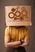 Young man gesturing with a cardboard box on his head with spur w — Stock Photo