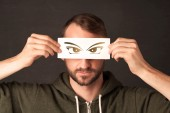 Cool youngster looking with a paper hand drawn eyes — Stock Photo