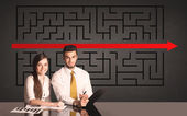 Business couple with a solved puzzle in background — Stock Photo