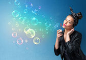 Pretty lady blowing colorful bubbles on blue background — Stock Photo