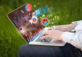 Hand typing on modern laptop notebook computer with graph icons  — Stock Photo