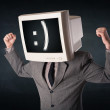Funny young businessman with a monitor on his head and smiley on — Stock Photo #69051301