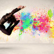 Happy teenager jumping with colorful ink splatter on urban backg — Stock Photo #69235819