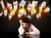 Depressed businessman sitting under burning tax and bill papers — Stock Photo