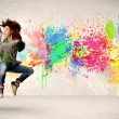 Happy teenager jumping with colorful ink splatter on urban backg — Stock Photo #69839479