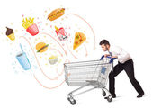 Man with shopping cart with toxic junk food — Stock Photo